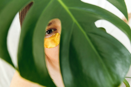 Eye Skin Care and Treatment. Portrait of beautiful young woman with golden eye patch under green palm leaf, creative beauty photo. Girl with lifting anti-wrinkle collagen patches under eyes. Cosmetics