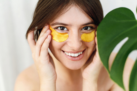 Portrait of beautiful young woman applying golden eye patches at green monstera leaf on white. Happy girl with natural skin and lifting anti-wrinkle collagen patches under eyes. Beauty Cosmetics Stock Photo
