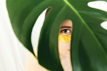 Portrait of beautiful young woman with golden patch under eye at green palm leaf, creative beauty photo. Girl with lifting anti-wrinkle collagen patches under eyes. Beauty Cosmetics. Eye Skin Care