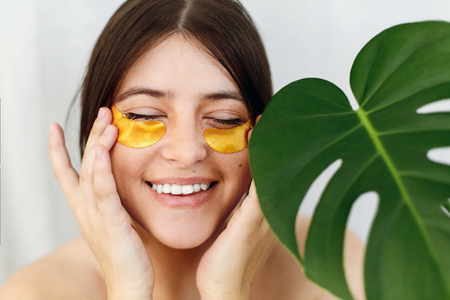 Happy girl with natural skin and lifting anti-wrinkle collagen patches under eyes. Beauty Cosmetics. Portrait of beautiful young woman applying golden eye patches at green monstera leaf on white.