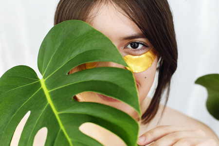 Happy girl with natural skin and lifting anti-wrinkle collagen patches under eyes and green palm leaf. Portrait of beautiful young woman with golden eye patches on white background. Eye Skin Care
