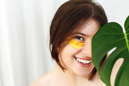 Happy girl with natural skin and lifting anti-wrinkle collagen patches under eyes and green palm leaf. Portrait of beautiful young woman with golden eye patches on white, copy space. Eye Skin Care