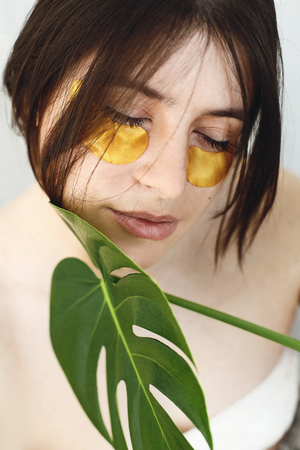 Eye Skin Care and Treatment. Portrait of beautiful young woman with natural makeup and golden eye patches at green monstera leaf. Natural skin care. Lifting anti-wrinkle collagen patches under eyes