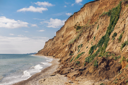 Beautiful view of sandy cliff near sea beach. Landscape of beach cliff and waves. Summer vacation concept. Exploring interesting places Imagens