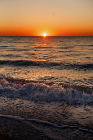 Beautiful view of sunrise in sea. Close Up of waves and beach at sea and colorful sky during sun rise, atmospheric moment. Sunset, dusk or dawn horizon in ocean. Summer vacation on tropical island