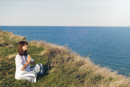 International Yoga day concept. Young beautiful woman practicing yoga on beach, sitting in grass. Hipster girl doing yoga, relaxing and listening to sea waves. Meditation, calm, happiness.