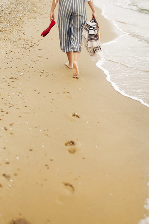 Woman walking barefoot on beach, back view of legs. Young girl relaxing on sandy beach, walking with shoes and bag in hands. Summer vacation concept