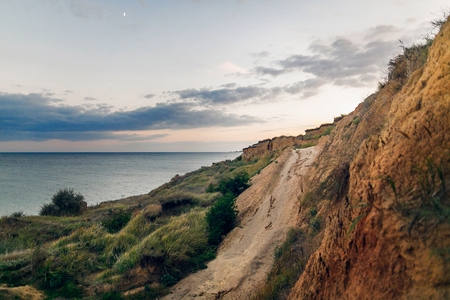 Beautiful view of sandy cliff near sea beach in sunset. Landscape of beach cliff and waves and cloudy sky in sunset or sunrise. Summer vacation concept. Exploring interesting places Imagens