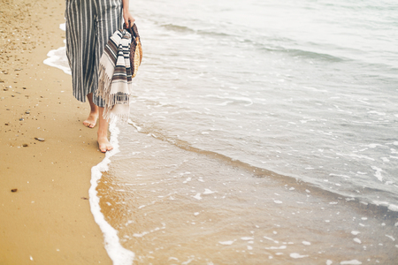 Woman walking barefoot on beach, close up view of legs and waves. Young girl relaxing on sandy beach near sea, walking with bag in hand. Summer vacation concept
