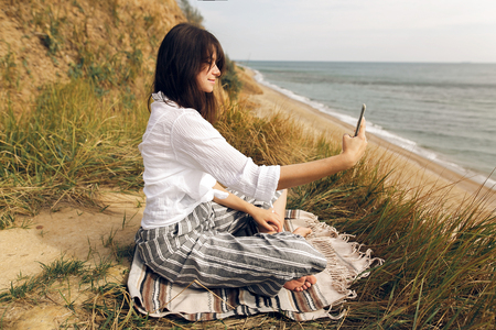 Young beautiful woman practicing yoga on beach, sitting in grass and looking at phone, taking selfie. Hipster girl doing yoga, relaxing and meditatiig.International Yoga day concept.