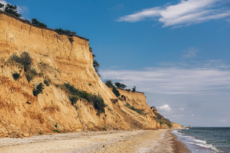 Beautiful view of sandy cliff near sea beach. Landscape of beach cliff and waves in sunny weather. Summer vacation concept. Exploring interesting places