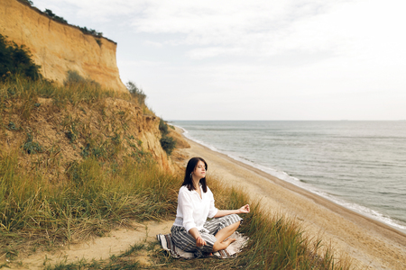 Young beautiful woman relaxing and practicing yoga on beach, sitting in grass and sand, meditating and listening to sea waves. Hipster girl doing yoga. Meditation,calm and happiness. Yoga day Stock Photo