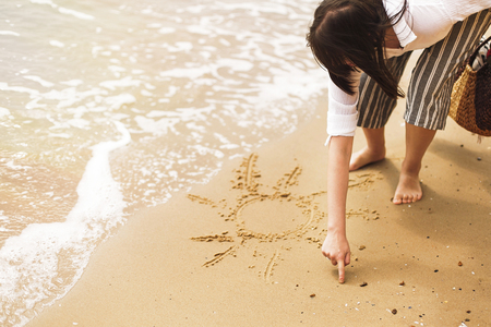 Young woman writing sun on sand beach near sea and waves. Hipster girl relaxing on sandy beach, walking and having fun. Summer vacation concept Stock Photo