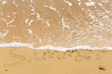 Hello summer concept. Summer text written on sandy beach and sea waves. Relaxing on tropical island. Summer vacation concept Stock Photo