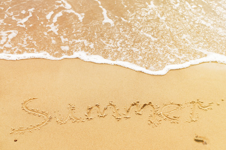 Summer text written on sandy beach and sea waves. Relaxing on tropical island. Summer vacation concept. Hello summer concept.
