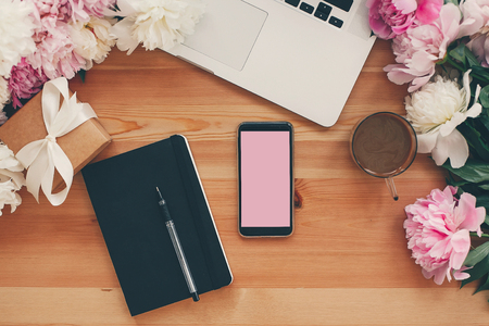 Stylish phone with empty screen, laptop, coffee cup, notebook,gift with pink and white peonies on table flat lay with space for text. Freelance concept. Stylish working place. Stock Photo
