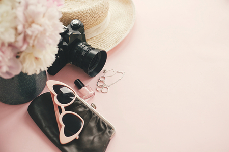 Hello summer.  International womens day. Stylish photo camera, sunglasses, jewelry,straw hat, cosmetics,bag pink and white peonies bouquet on pink paper with space for text.