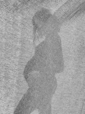Silhouette of stylish pregnant woman in stylish black dress holding belly bump and posing in light. Stylish fashionable mom, hugging belly, waiting for baby. Creative photo through textile Stockfoto
