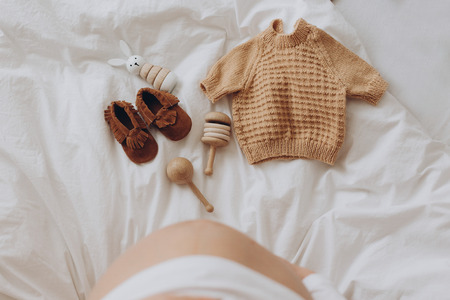 Top view of pregnant woman belly bump and stylish brown boho shoes, clothes and wooden toys for baby on white bed at home. Stylish pregnant mom waiting for baby. Motherhood concept
