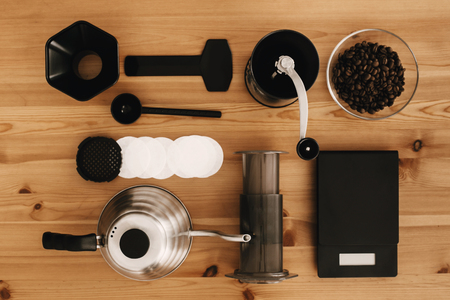 Steel kettle, scale, filter, manual grinder, aeropress, coffee beans top view. Alternative coffee brewing method, flat lay. Stylish accessories and items for alternative coffee on wooden table.