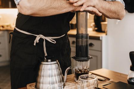 Barista professionnel préparant du café en aéropresse, méthode alternative de préparation du café. Mains sur aéropresse et tasse en verre, balances, broyeur manuel, grains de café, bouilloire sur table en bois Banque d'images