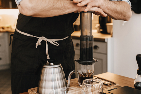 Professional barista preparing coffee in aeropress, alternative coffee brewing method. Hands on aeropress and glass cup, scales, manual grinder, coffee beans, kettle on wooden table Standard-Bild - 119391981