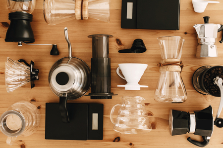 Kettle, scales, geyser, grinder, aeropress, pour over, glass flask top view. Alternative coffee brewing method set, flat lay. Stylish accessories and items for alternative coffee on wooden table.