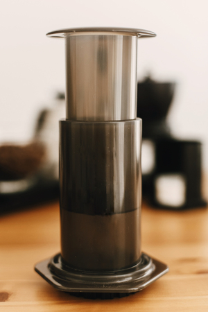 Aeropress, steel kettle, electronic scales, manual grinder, coffee beans,filters on wooden table. Alternative coffee brewing method set. Stylish accessories and items for alternative coffee