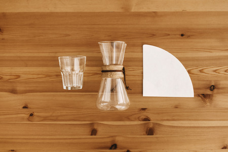 Alternative coffee brewing method, flat lay. Stylish accessories and items for alternative coffee on wooden table. Glass cup, paper filter, glass flask top view. Making coffee