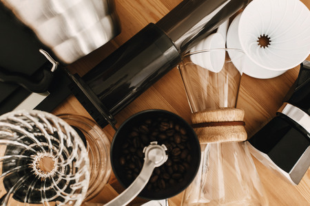 Kettle, scales, geyser, grinder, aeropress, pour over, glass flask top view. Alternative coffee brewing method set, flat lay. Stylish accessories and items for alternative coffee on wooden table. Reklamní fotografie - 119391891