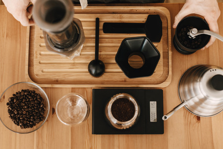 Flat lay of hands, aeropress, scales, manual grinder, ground coffee and beans, kettle on wooden table. Professional barista preparing coffee aeropress alternative method, brewing process Stockfoto