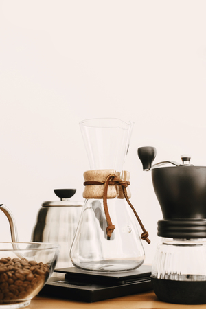 Alternative coffee brewing method set. Stylish accessories and items for alternative coffee on wooden table. Steel kettle, electronic scales, manual grinder and glass flask and filter on wood