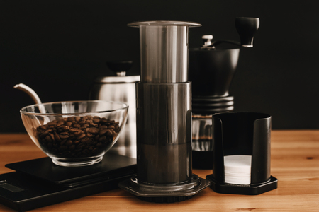 Aeropress, steel kettle, scales, manual grinder, coffee beans on wooden table and black background. Alternative coffee brewing method set. Stylish accessories and items for alternative coffee