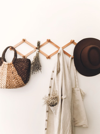 Stylish wooden hanger with straw bag, linen tote bag, brown hat and linen cloth. Countryside still life. Zero waste home concept. Sustainable lifestyle. Phone photo