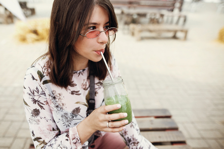 Stylish hipster boho girl drinking spinach smoothie in glass jar with metal reusable straw at street food festival. Happy woman in sunglasses with healthy drink in summer street. Zero waste