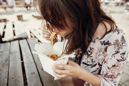 Stylish hipster girl eating wok noodles with vegetables and seafood from carton box with bamboo chopsticks. Asian Street food festival. Boho woman eating thai noodles in paper box takeaway 스톡 콘텐츠
