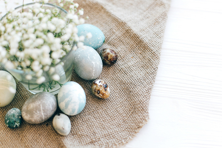 Stylish Easter eggs  on rustic fabric with spring flowers on white wooden background, flat lay with space for text. Modern colorful easter eggs painted with natural dye. Happy Easter