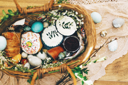 Stylish Easter basket with modern eggs, easter bread cake, ham, beets, sausage, butter and green branches on rustic fabric with spring flowers in sunny light. Top view. Happy Easter concept Stock Photo