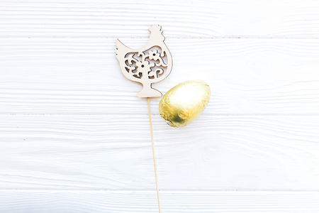 Stylish Easter chocolate egg in golden foil and simple wooden chicken decoration on white wooden background, flat lay with space for text. Happy Easter. Holiday gift and decor