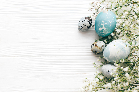 Happy Easter. Stylish Easter eggs with spring flowers border, flat lay on white wooden background with space for text. Modern easter eggs painted with natural dye in blue and grey marble.