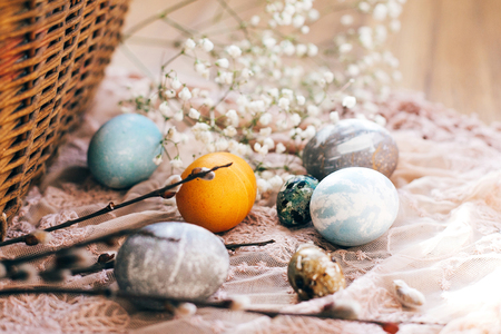 Stylish Easter eggs with spring flowers and willow branches on rustic fabric at wicker basket with holiday food in sunny light. Modern easter eggs painted with natural dye. Happy Easter Stock Photo