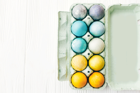 Happy Easter. Stylish Easter eggs in rainbow pastel colors in carton tray on white wooden background, flat lay with space for text. Modern colorful easter eggs painted with natural dye Standard-Bild - 119469456