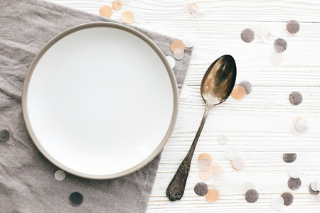 Diet concept. Stylish empty plate with vintage spoon on napkin on white table with confetti, flat lay. Modern set, serving for reception and party celebration.