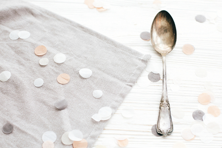 Stylish vintage spoon and grey linen napkin on white table with confetti, top view. Diet concept. Modern serving for reception and party celebration
