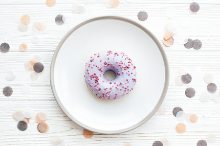 Delicious colorful donut with sprinkles on stylish plate on white table with confetti, flat lay. Party concept. No diet. Candy bar at wedding reception. Purple donut Stock Photo