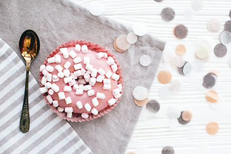 Delicious colorful pink donut with sprinkles and marshmallows on stylish white table with confetti and vintage spoon, flat lay. Party concept. No diet. Candy bar at wedding reception. Stock Photo