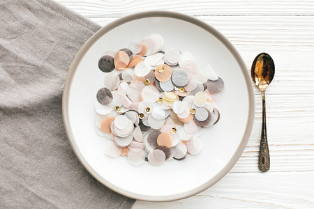 Stylish plate with golden confetti and vintage spoon on napkin on white table, flat lay. Modern set, serving for reception and celebration. Party and diet concept