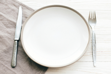 Stylish empty plate with vintage fork and knife on napkin on white table, top view. Modern set, serving for reception and celebration. Party and diet concept Stock Photo