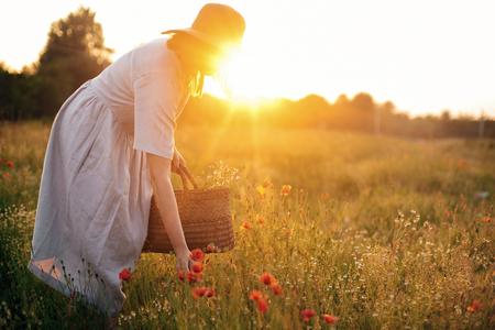 Stylish girl in linen dress gathering flowers in rustic straw basket, walking in poppy meadow in sunset. Boho woman in hat relaxing in warm evening sunlight in summer field