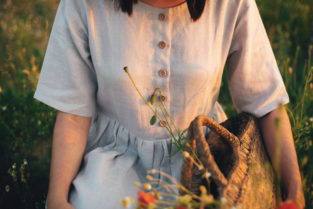 Stylish girl in linen dress gathering flowers in rustic straw basket, sitting in poppy meadow in sunset. Boho woman holding wildflowers bud in warm sunlight in summer field. Banque d'images